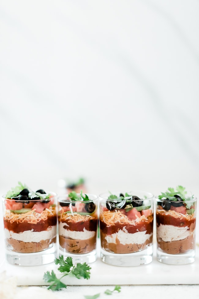 7 layer dip recipe in individual glasses, lined up.