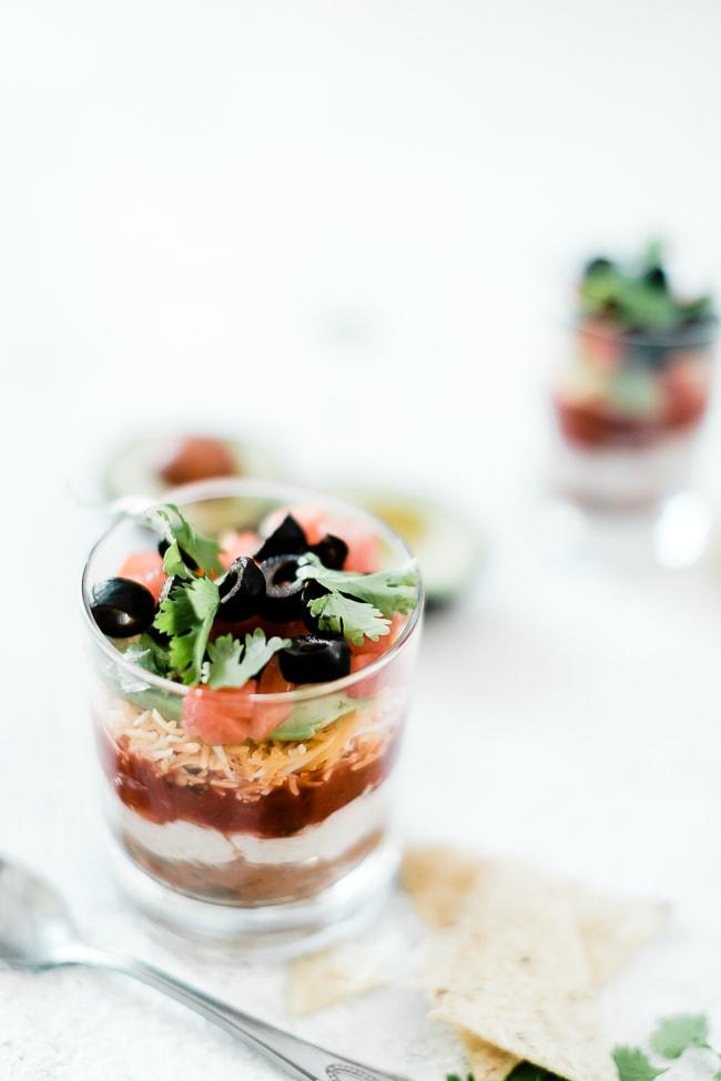 Individual 7 layer dip recipe in a glass juice glass.