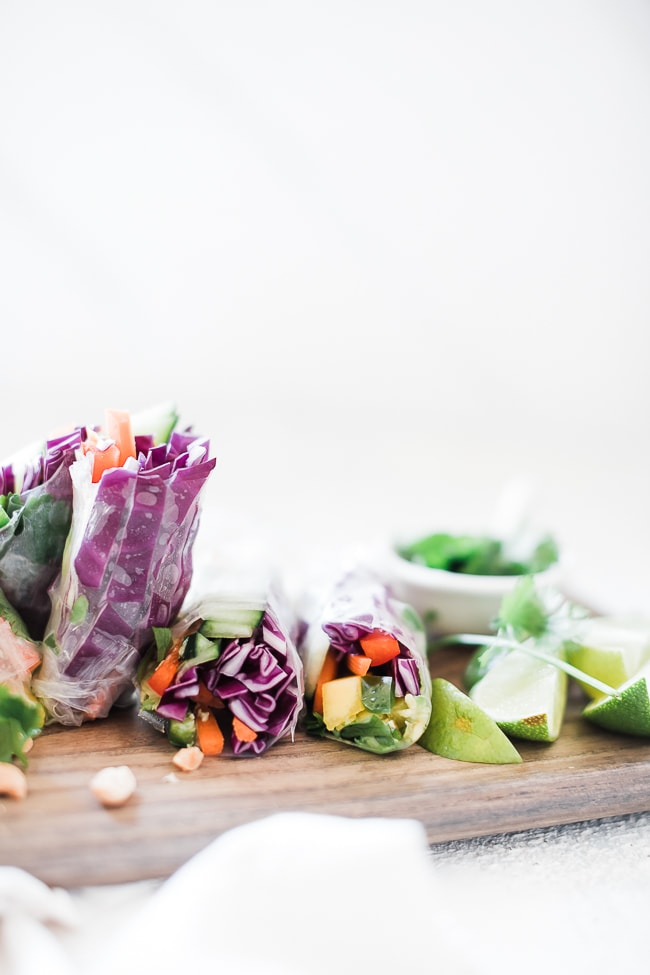 Easy spring roll recipe arranged on a wooden cutting board. Peanut dipping sauce and peanuts to the side.