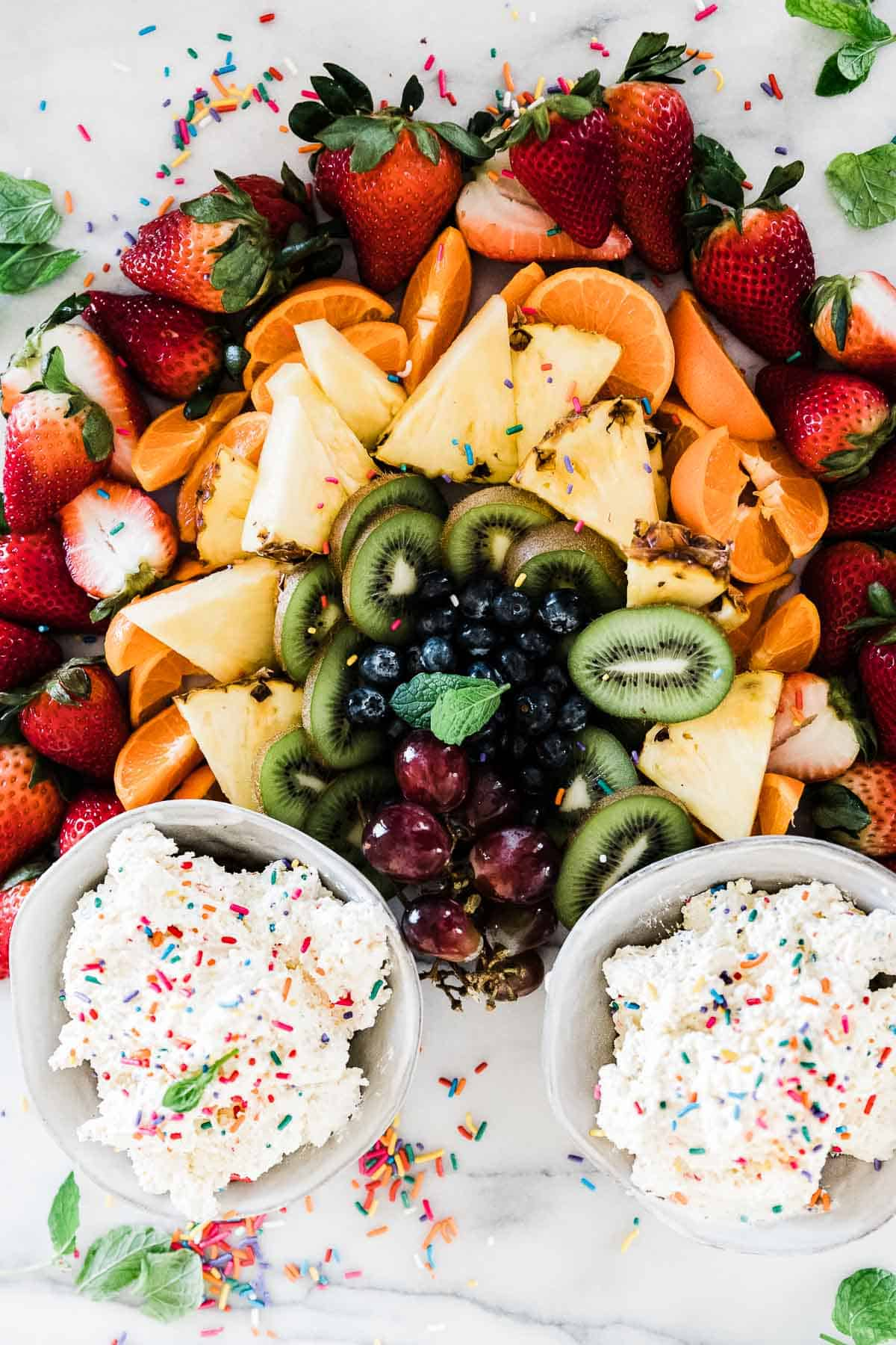 Funfetti cake batter dip on a tray of crackers and fruit.
