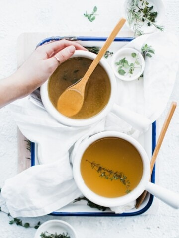 two bowls of broth with a hand around one of them