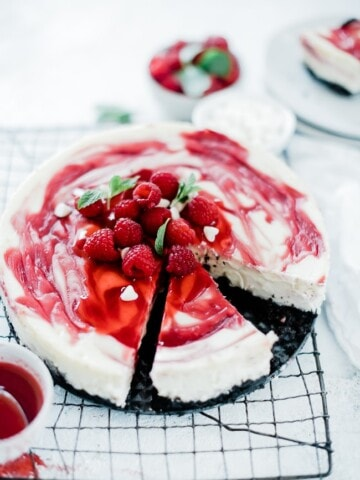 white chocolate raspberry cheesecake recipe on a wire cooling rack.