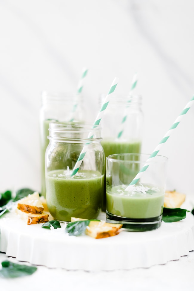 Green Pina colada smoothie in various sized glasses on a white platter.