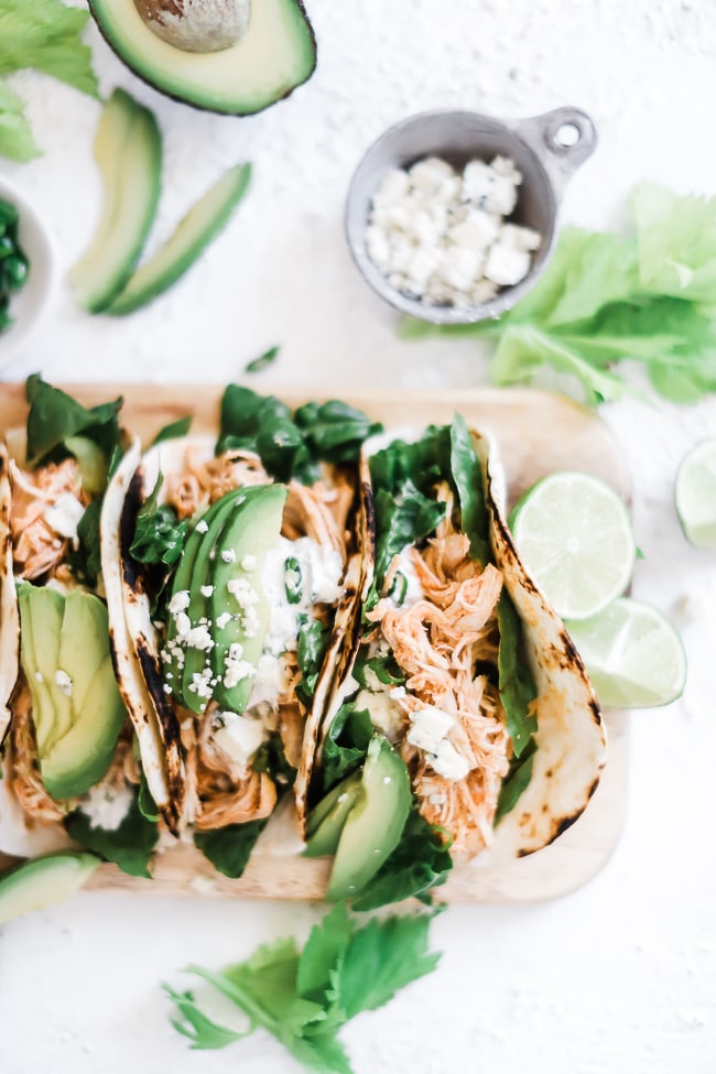 Buffalo chicken tacos topped with avocado and blue cheese crumbles.