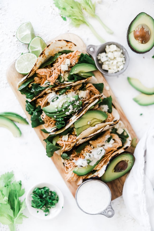 Buffalo chicken tacos on a wooden cutting board.
