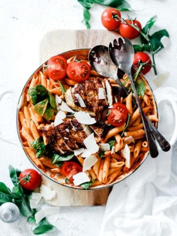 Penne rose in a white braiser, garnished with spinach.