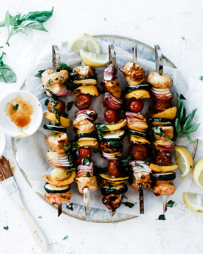 Chicken skewers on a metal platter, garnished with basil and lemon.