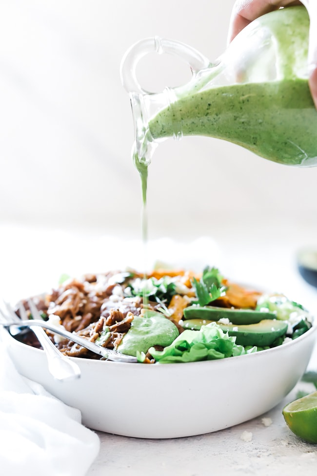 Cilantro dressing being poured from a glass bottle onto a salad of greens, sweet shredded pork, tortilla strips, and avocado.