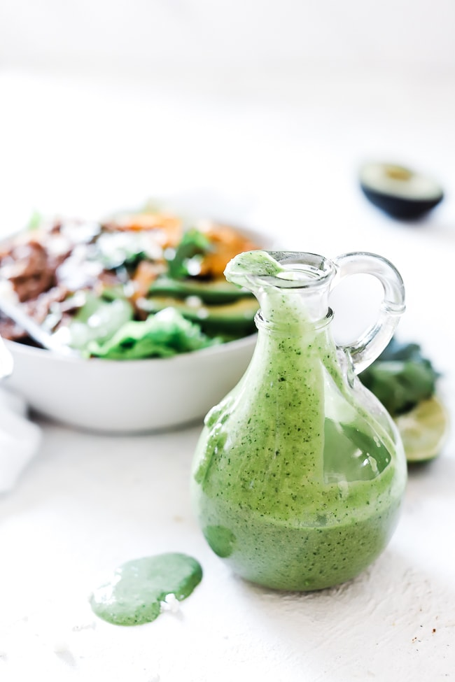 Green dressing in a glass bottle. Set in front of a cafe rio style salad.