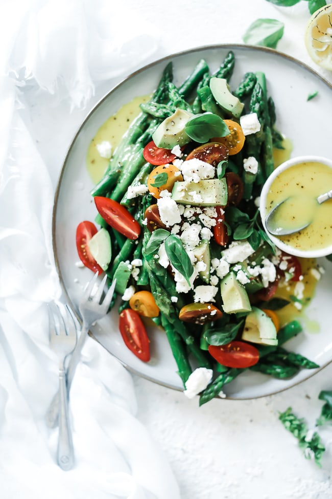 Summer asparagus salad recipe on a large white platter, garnished with basil and Feta cheese.