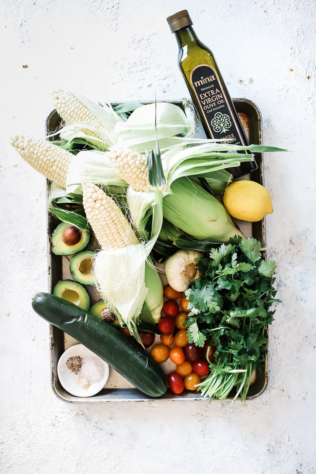 Ingredients for summer corn salad - corn, cucumber, avocado, tomato, cilantro, lime, olive oil, spices.