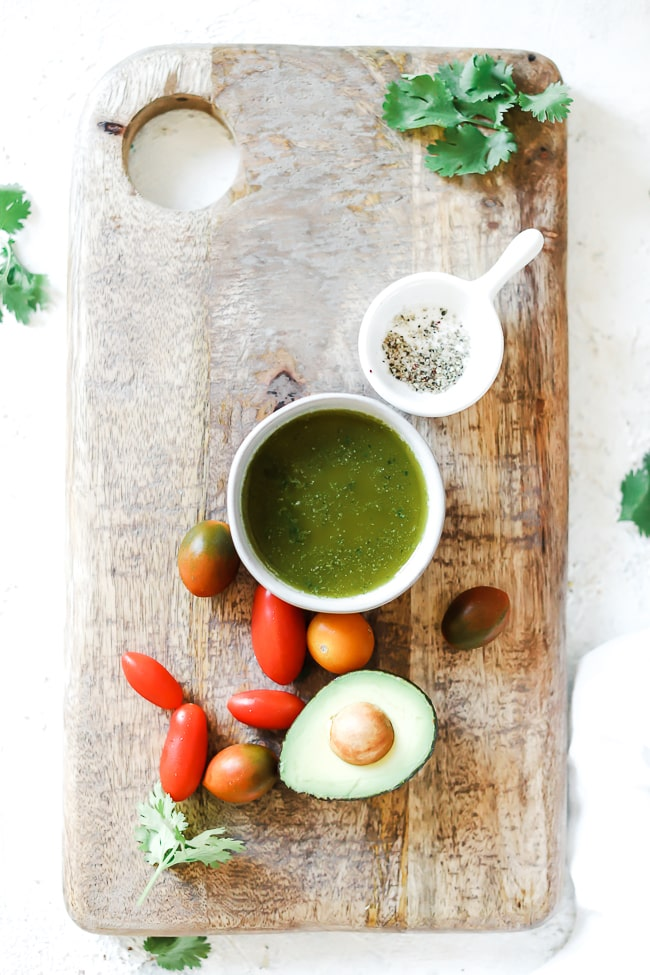 Cilantro vinaigrette on a wooden cutting board, in a small bowl with tomatoes and avocado to the side.