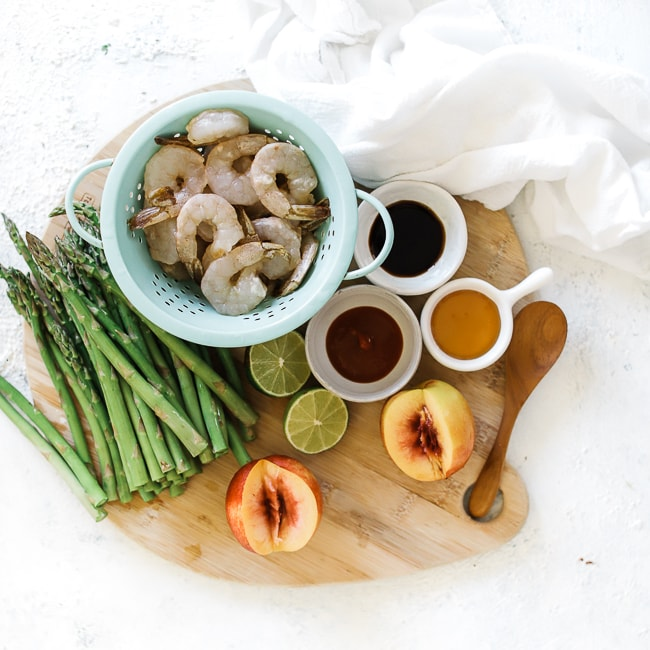Ingredients needed for making peach and grilled shrimp kabobs - shrimp, asparagus. peaches, limes, soy sauce, sriracha, honey.