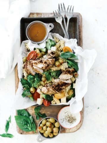 Summer pasta salad recipe in a metal baking tray. There is a bowl of dressing to the side as well as 3 forks. The pan is placed on top of a wooden cutting board.