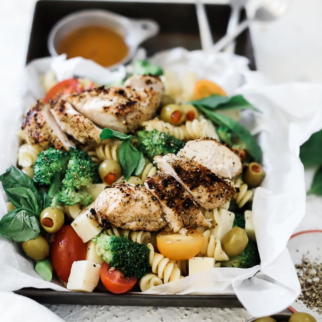 A close up of summer pasta salad in a metal baking dish.