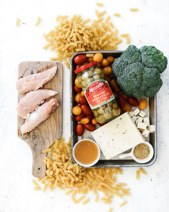 Ingredients needed for pasta salad - pasta, chicken, olives, tomatoes, cheese, broccoli, and dressing - all placed in a baking sheet.