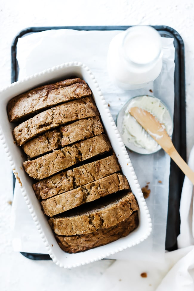 Easy zucchini bread in a white loaf pan. The bread is sliced.