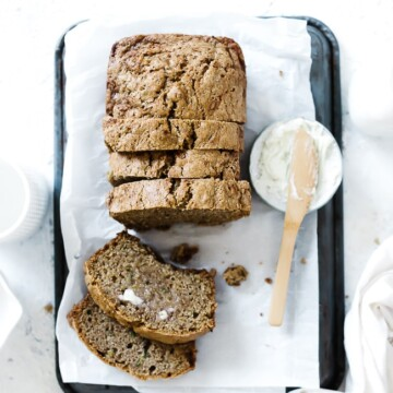 Easy zucchini bread atop a piece of white parchment paper. The bread is slices and there is a pat of butter to the side.
