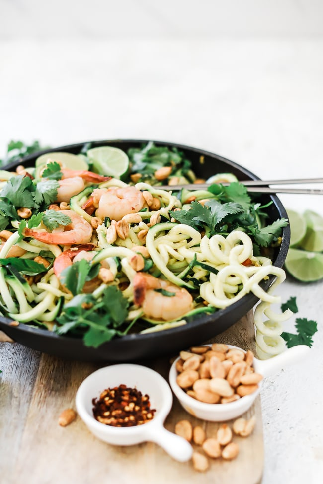 A 3/4 view of noodles pan Thai. There are zucchini noodle falling gout of the pan. The dish is garnished with lots of cilantro, and there are small dishes of peanuts and crushed red pepper to the side.