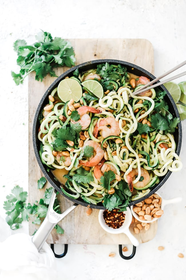 Shrimp pad thai recipe in a ninja skillet. The dish is garnished with cilantro and peanuts. There are small dishes of peanuts and crushed red pepper to the side.