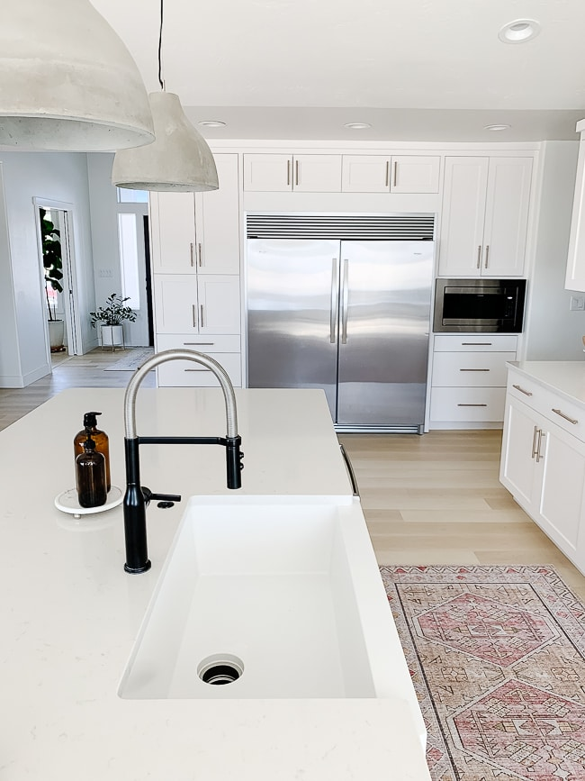 white sink black faucet with built in fridge in background