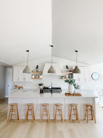 kitchen with white bar and 6 barstools, hanging cement pendants