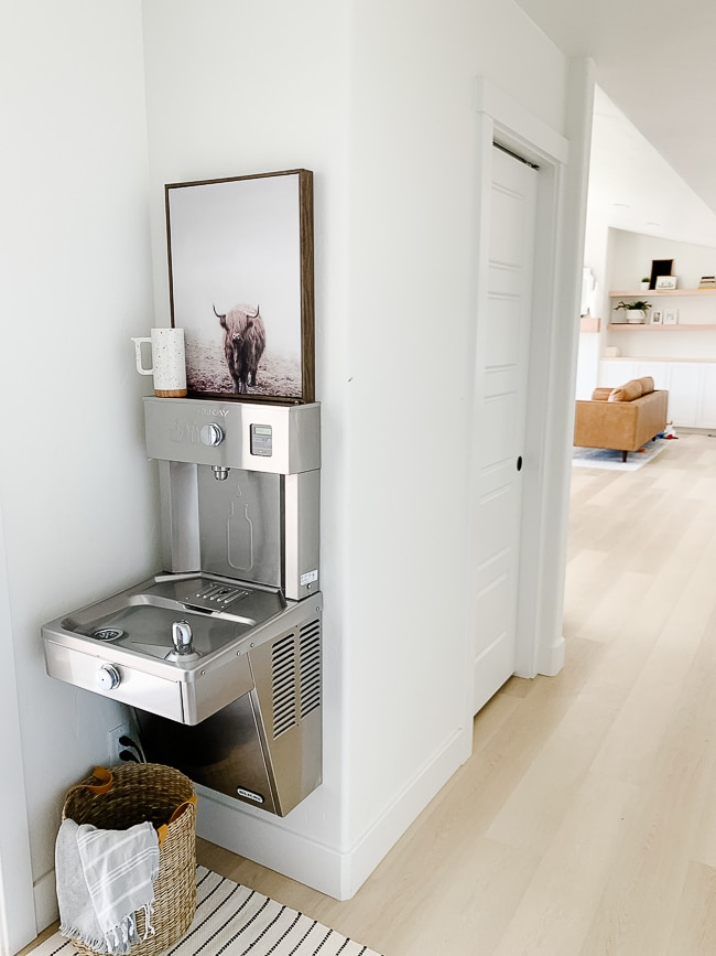 drinking fountain mounted on wall with basket under