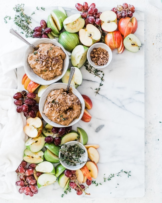 A marble platter filled with green and red apples, grapes, and two bowls of toffee apple dip.