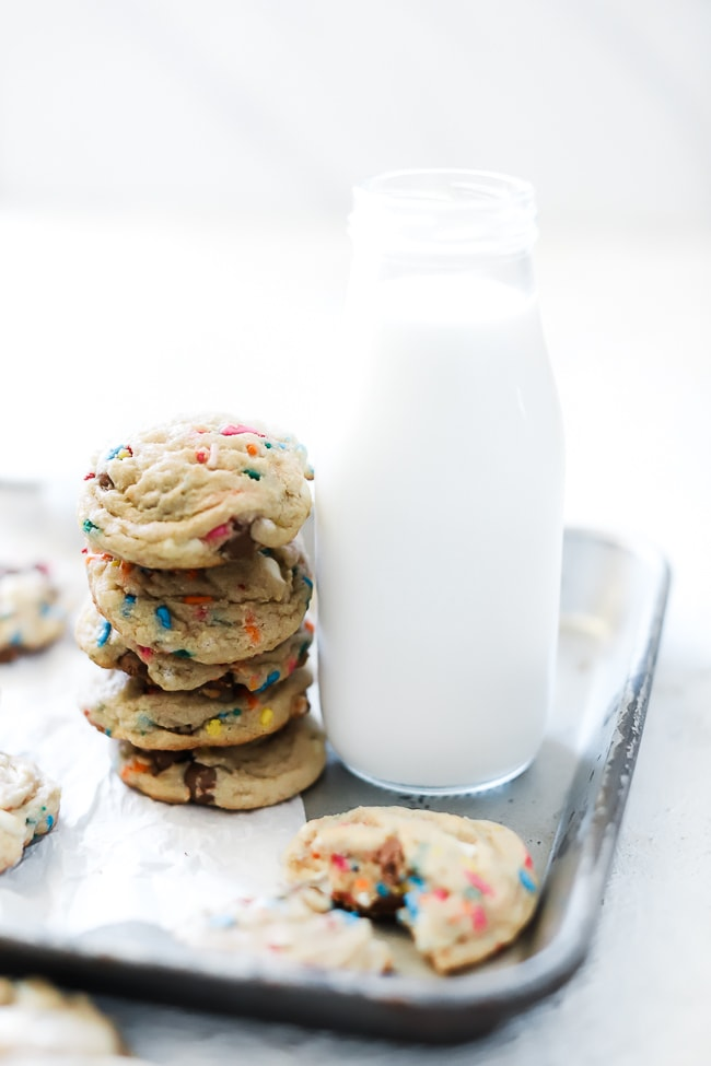 Birthday cake cookies on a baking sheet next to a glass of milk
