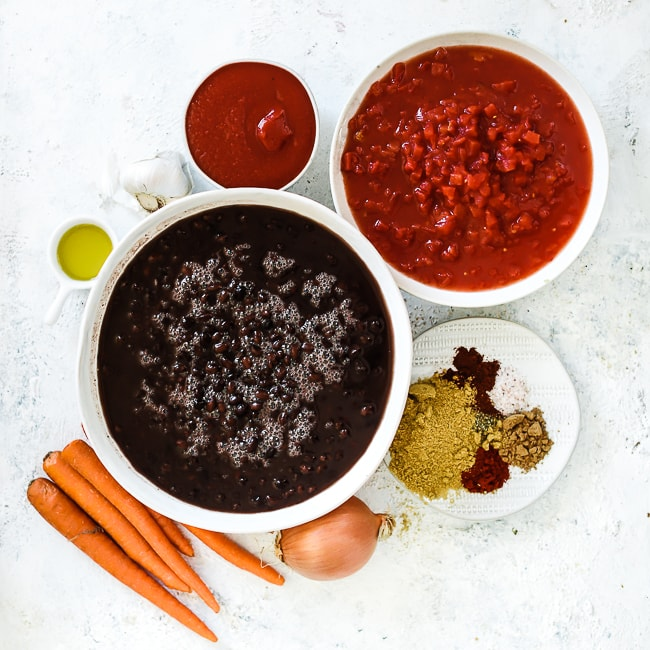 Ingredients needed to make black bean soup in bowls: black beans, tomatoes, carrots, spices.
