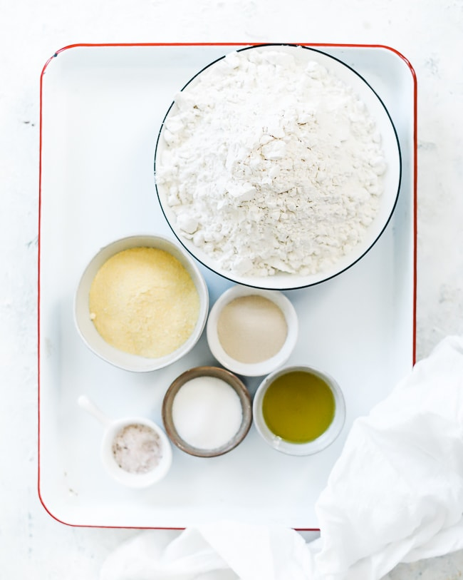 Ingredients needed for how to make bread bowls. They are on a baking sheet and include flour, cornmeal, yeast, sugar, oil, and salt.