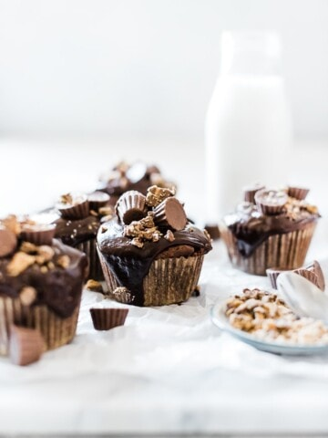 Chocolate peanut butter cupcakes on a marble tray. There is a bottle of milk to the side.