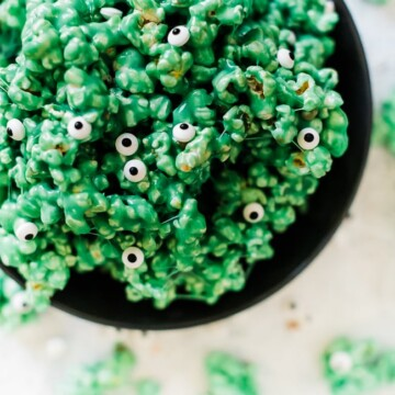 Monster halloween popcorn in a large black bowl. The popcorn is green with candy eyeballs.