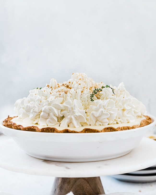 A straight on shot of easy banana cream pie recipe in a white pie plate. The pie is sitting atop a cake stand.
