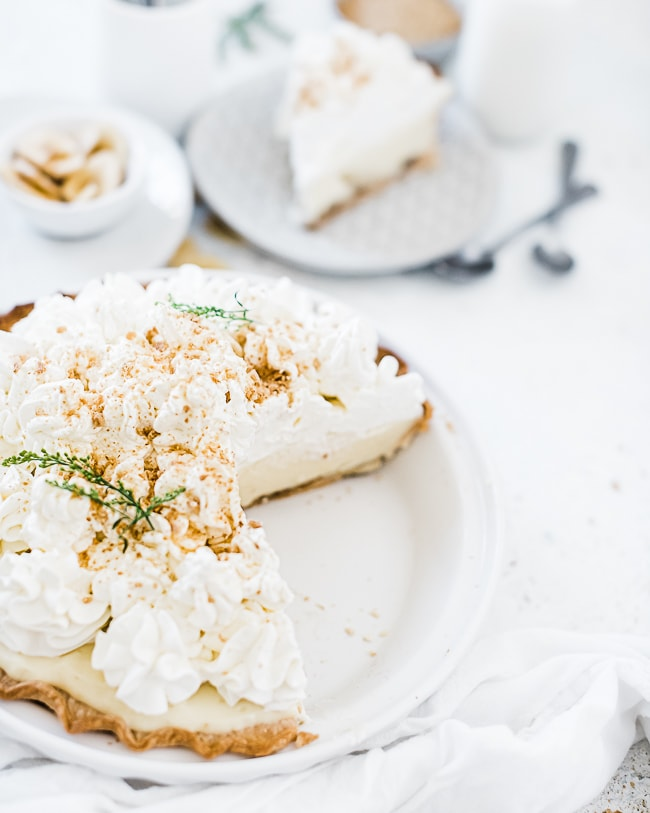 Easy banana cream pie recipe in a white pie plate. There is a large slice missing form the pie.