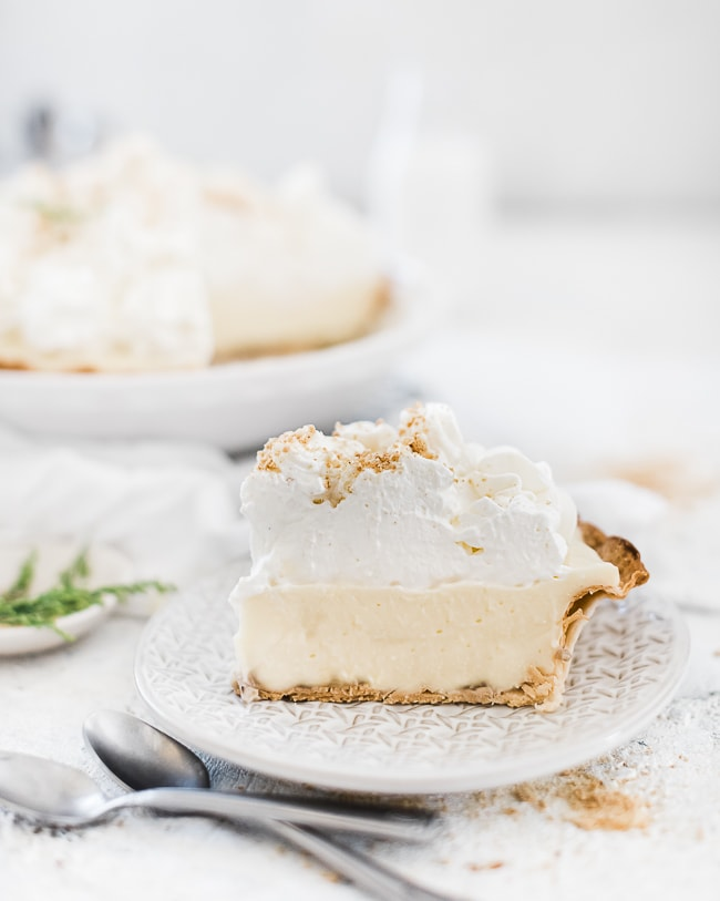 Easy banana cream pie recipe sliced on a dessert plate. There are two spoons to the side.