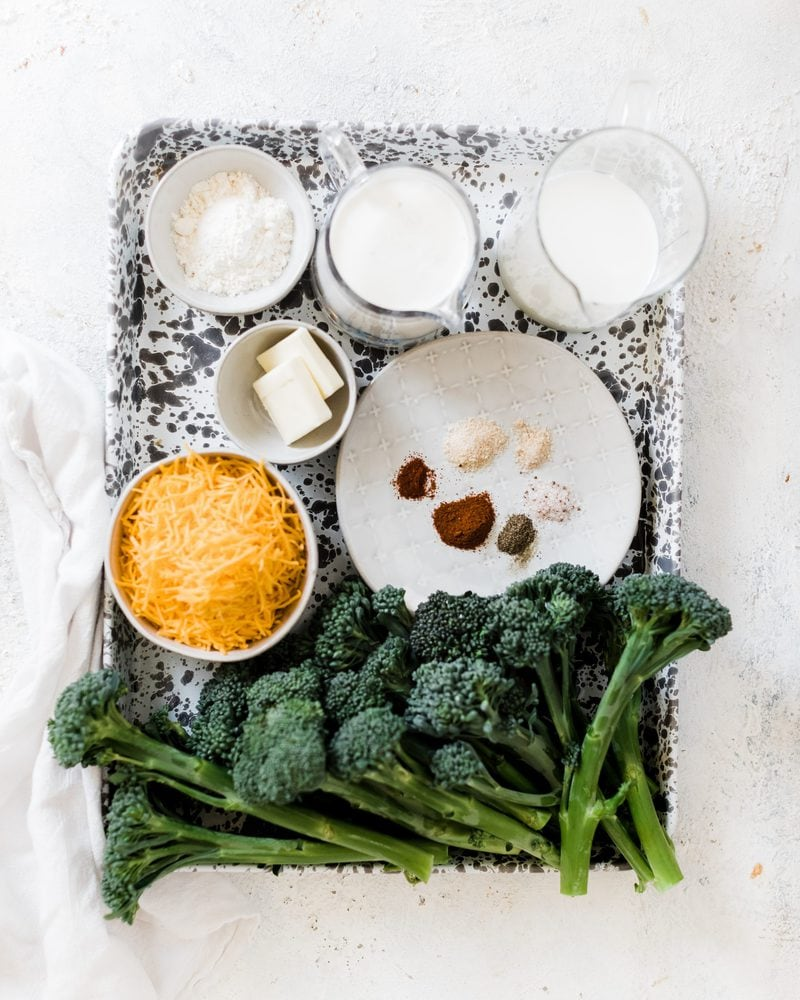 Ingredients needed from broccoli and cheese sauce on a marbled baking sheet: broccoli, cheese, milk, butter, flour and spices.