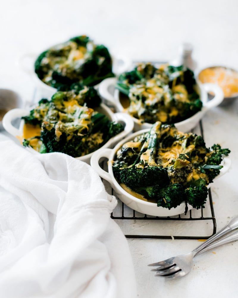 Small dishes of broccoli and cheese sauce on a cooling rack.