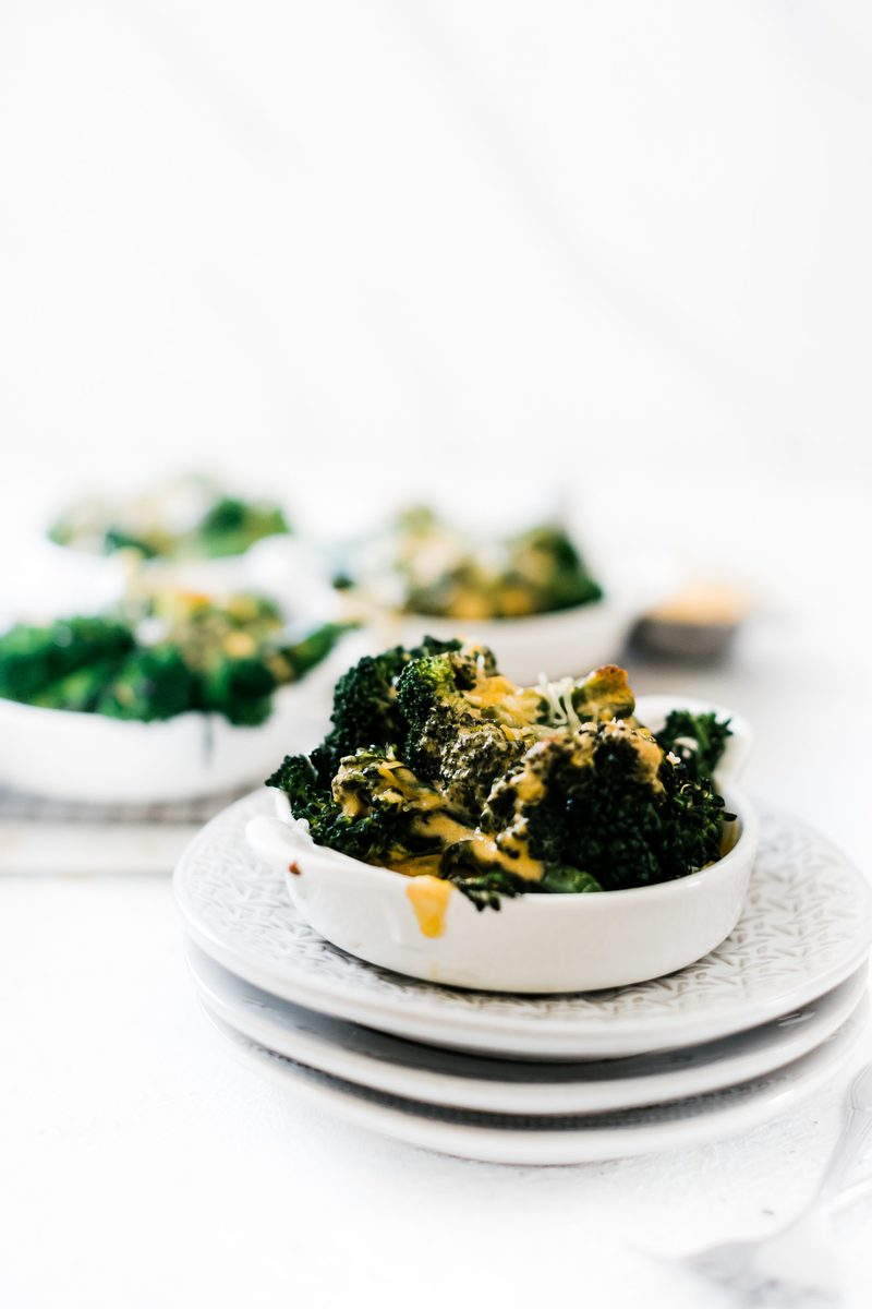 Broccoli and cheese sauce in a handled tart dish atop a stack of plates.