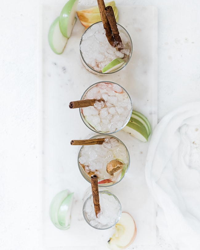 An overhead shot of Apple pie fruit water recipe in glasses filled with ice atop a marble tray.