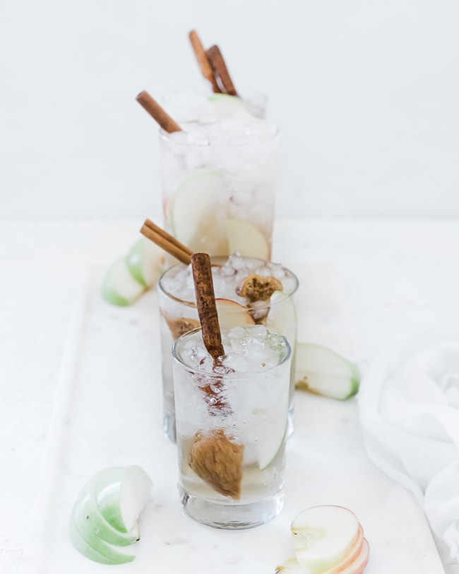 Apple pie fruit water recipe in glasses filled with ice atop a marble tray.