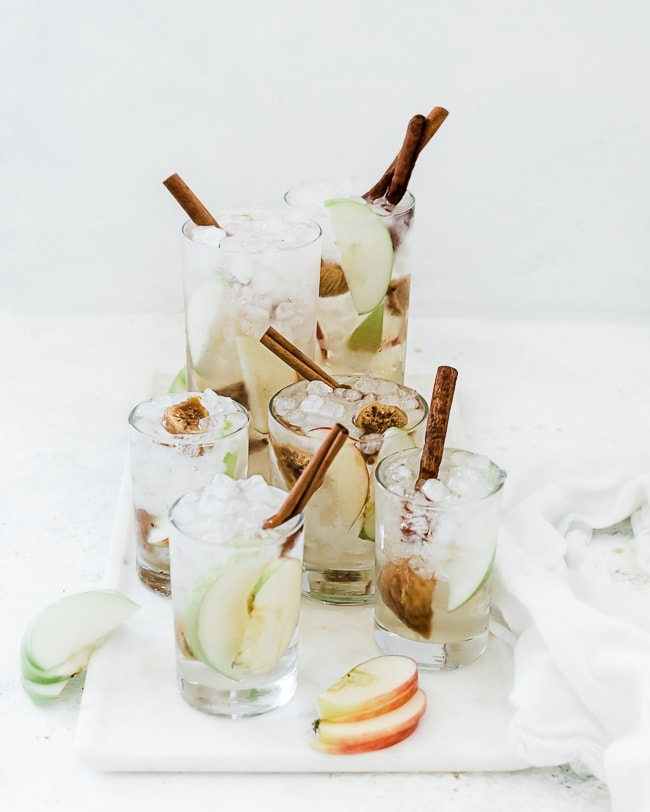 Glasses filled with apple pie fruit water recipe. Drinks are garnished with cinnamon sticks and there are apple slices scattered around.
