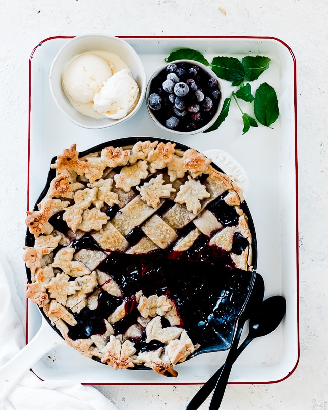 Razzleberry pie made in a cast iron skillet. The pan is placed in a white baking pan.