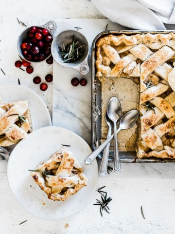 Slab pie baked in a metal sheet pan. There are slices on dessert plates to the side.