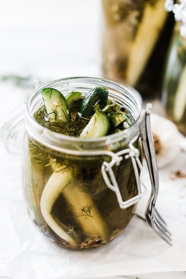 A close up of garlic dill pickle recipe in a glass hinged jar. The jar is open and pickles are poking out.