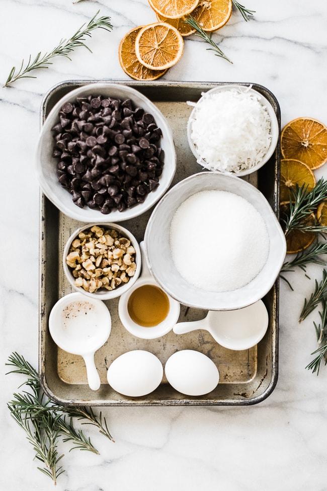 Ingredients needed to make chocolate meringue cookies on a metal baking tray.