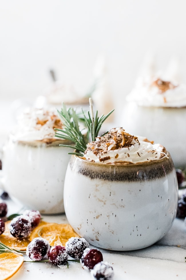 Coconut milk hot chocolate in white mugs. They are topped with whipped cream and garnished with rosemary.