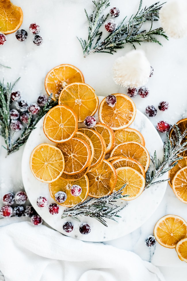 Dried orange slices on a marble tray surrounded by sugared cranberries and rosemary.