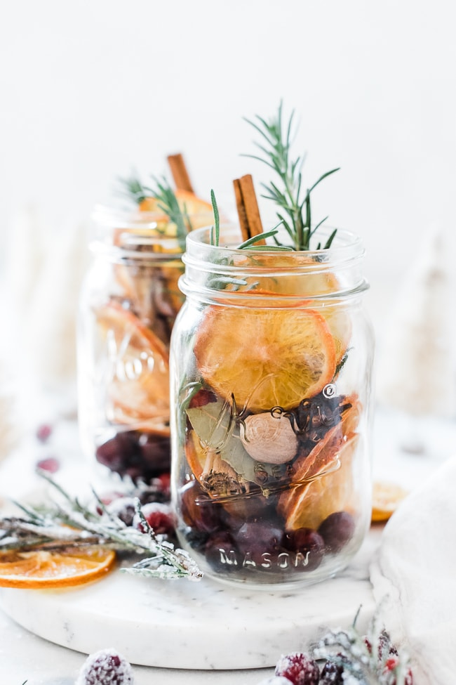 Two mason jars filled with An overhead shot of Stovetop Potpourri. There is sugared rosemary and cranberries surrounding the jars.