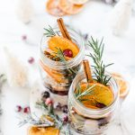 Stovetop Potpourri in glass mason jars. There are bottle brushes, rosemary, cranberries, and orange slices surrounding.